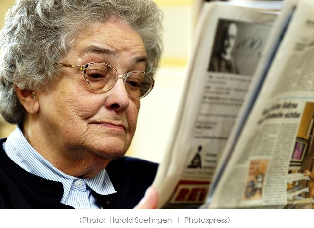 Old woman reading newspaper.